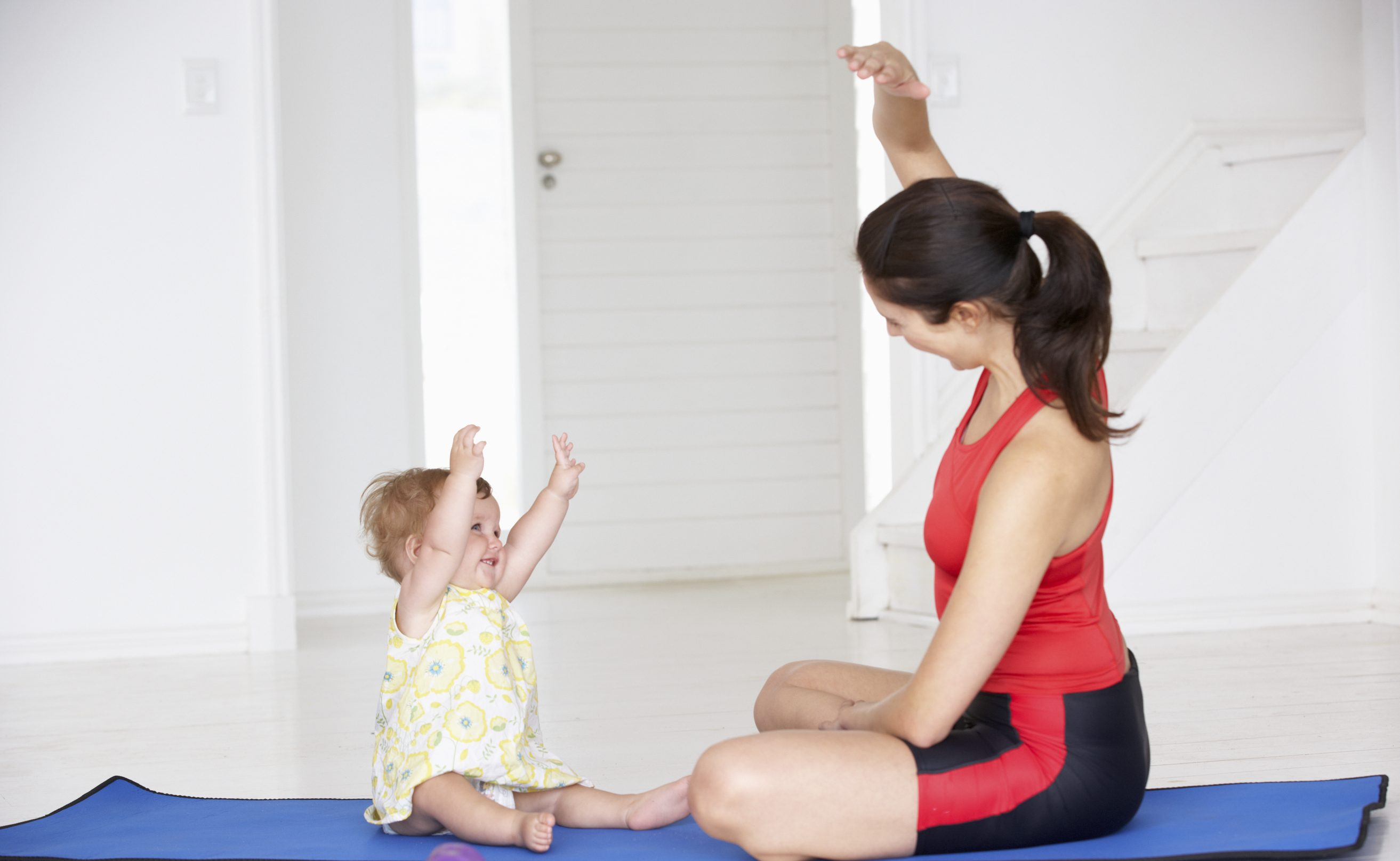 Mother and baby doing yoga at home